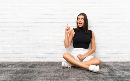 Pretty young woman sitting on the floor intending to realizes the solution while lifting a finger up Reklamní fotografie
