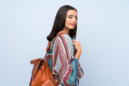 Young woman over isolated blue wall with backpack