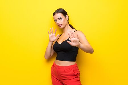 Young woman over isolated yellow background nervous stretching hands to the front