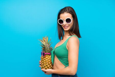 Young woman in swimsuit in summer holidays holding a pineapple with sunglasses Banque d'images