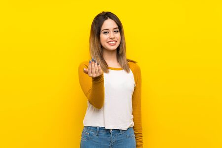 Pretty young woman over isolated yellow wall inviting to come with hand. Happy that you came Imagens