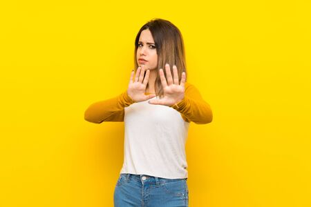 Pretty young woman over isolated yellow wall nervous stretching hands to the front Zdjęcie Seryjne