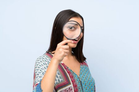 Young woman over isolated blue wall holding a magnifying glass