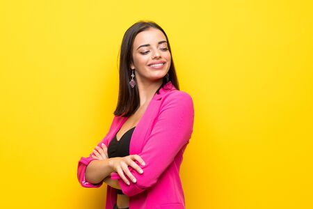 Young woman over isolated yellow background with arms crossed and happy