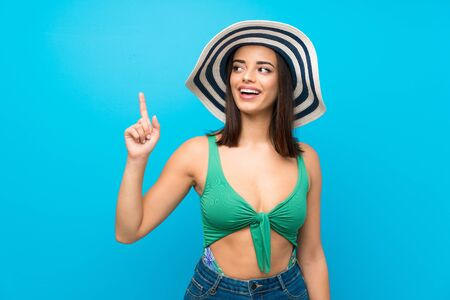 Young woman in swimsuit in summer holidays intending to realizes the solution while lifting a finger up Reklamní fotografie