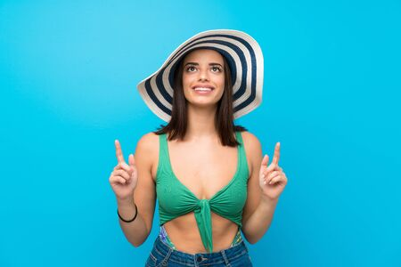 Young woman in swimsuit in summer holidays pointing up a great idea