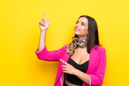 Young woman over isolated yellow background pointing with the index finger a great idea