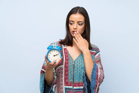Young woman over isolated blue wall holding vintage alarm clock