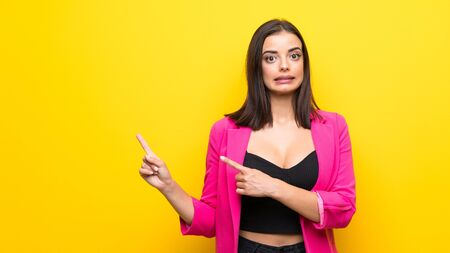 Young woman over isolated yellow background frightened and pointing to the side Zdjęcie Seryjne