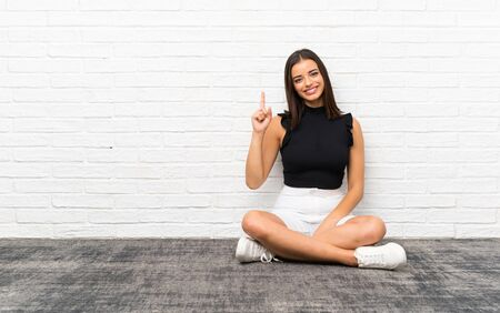 Pretty young woman sitting on the floor showing and lifting a finger in sign of the best Reklamní fotografie