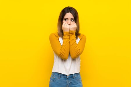 Pretty young woman over isolated yellow wall nervous and scared putting hands to mouth