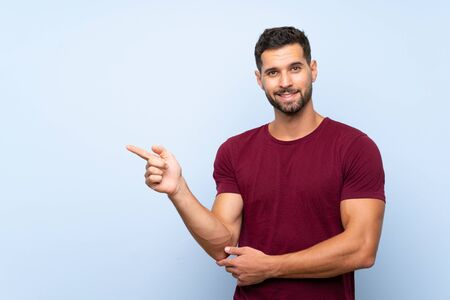 Handsome man over isolated blue background pointing finger to the side