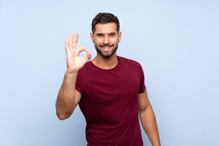 Handsome man over isolated blue background showing ok sign with fingers