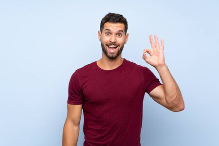 Handsome man over isolated blue background surprised and showing ok sign