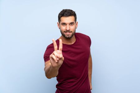 Handsome man over isolated blue background smiling and showing victory sign