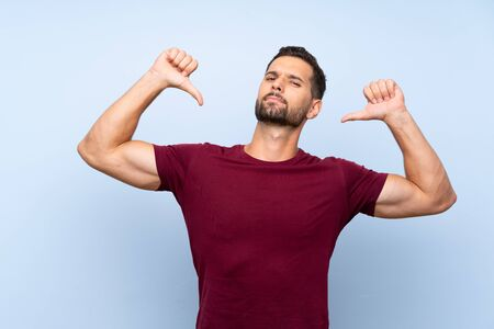 Handsome man over isolated blue background showing thumb down
