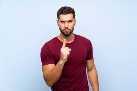 Handsome man over isolated blue background frustrated and pointing to the front