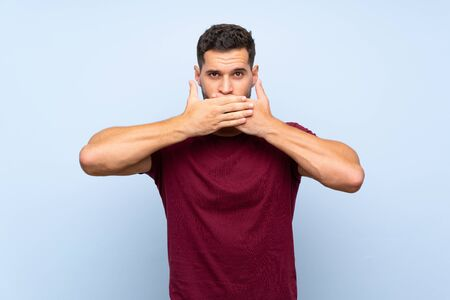 Handsome man over isolated blue background covering mouth with hands