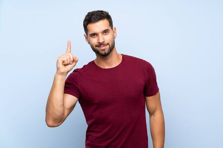 Handsome man over isolated blue background showing and lifting a finger in sign of the best Stock fotó