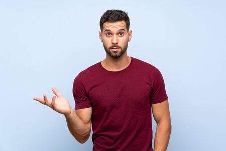 Handsome man over isolated blue background making doubts gesture Фото со стока