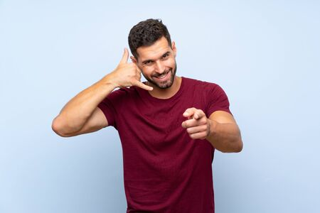 Handsome man over isolated blue background making phone gesture and pointing front Stock fotó