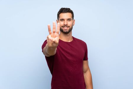 Handsome man over isolated blue background happy and counting three with fingers