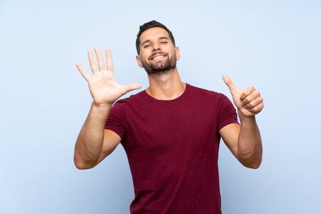 Handsome man over isolated blue background counting six with fingers Stock fotó