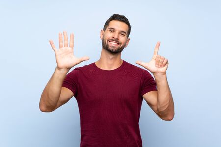Handsome man over isolated blue background counting seven with fingers