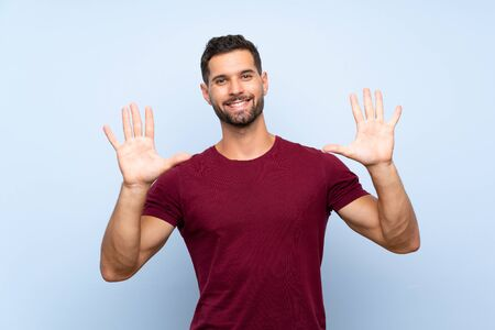 Handsome man over isolated blue background counting ten with fingers