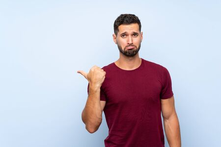 Handsome man over isolated blue background unhappy and pointing to the side