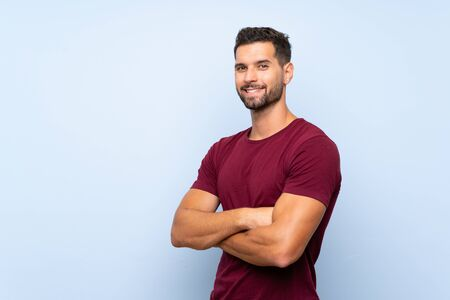Handsome man over isolated blue background with arms crossed and looking forward