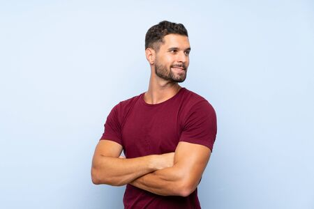 Handsome man over isolated blue background with arms crossed and happy Stock fotó