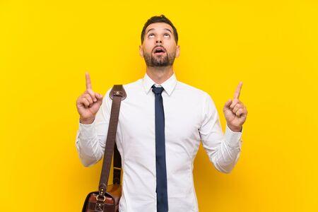 Bell'uomo d'affari su sfondo giallo isolato che punta con il dito indice una grande idea