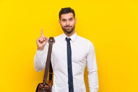 Apuesto hombre de negocios sobre fondo amarillo aislado apuntando con el dedo índice una gran idea Foto de archivo