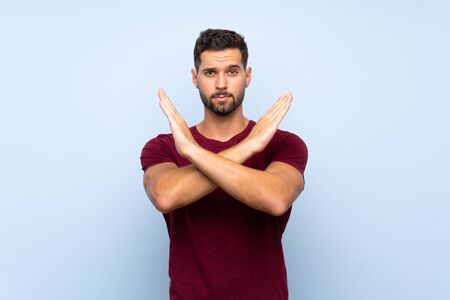 Handsome man over isolated blue background making NO gesture