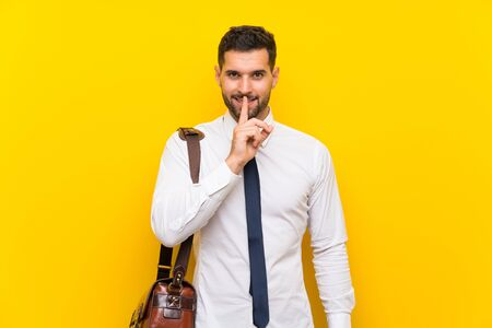 Handsome businessman over isolated yellow background doing silence gesture