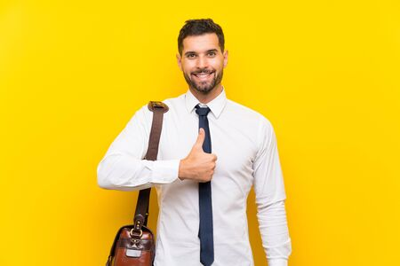 Handsome businessman over isolated yellow background giving a thumbs up gesture