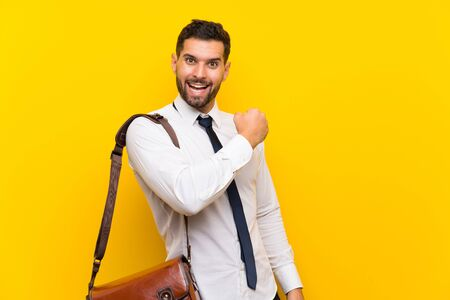 Handsome businessman over isolated yellow background celebrating a victory Stok Fotoğraf - 132036531