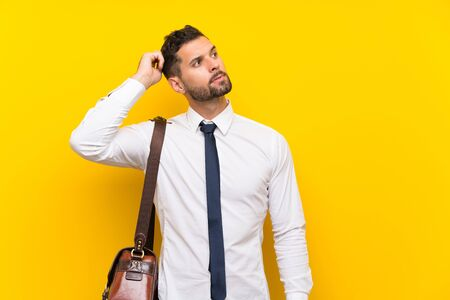 Handsome businessman over isolated yellow background having doubts and with confuse face expression