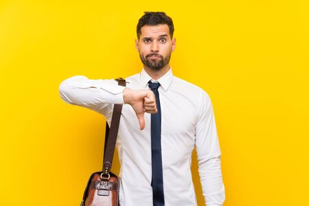 Handsome businessman over isolated yellow background showing thumb down sign Zdjęcie Seryjne