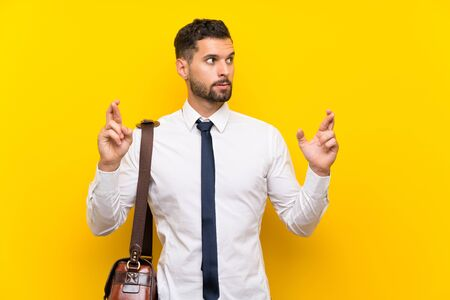 Handsome businessman over isolated yellow background with fingers crossing