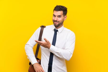 Handsome businessman over isolated yellow background extending hands to the side for inviting to come