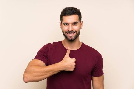 Handsome man over isolated background giving a thumbs up gesture