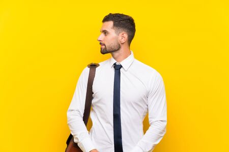 Handsome businessman over isolated yellow background looking to the side