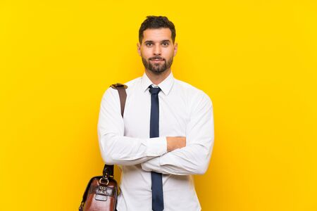 Handsome businessman over isolated yellow background keeping arms crossed