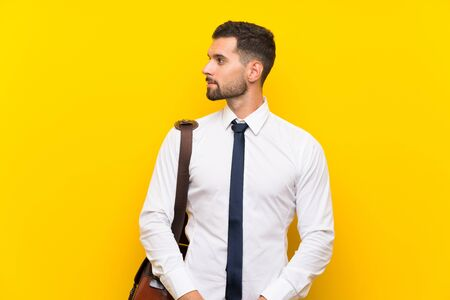 Handsome businessman over isolated yellow background looking side Zdjęcie Seryjne