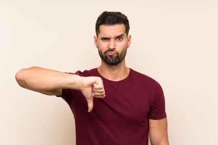 Handsome man over isolated background showing thumb down sign