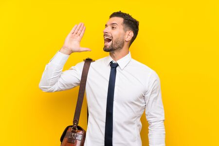 Handsome businessman over isolated yellow background shouting with mouth wide open