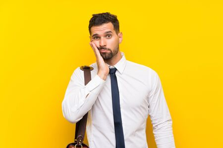 Handsome businessman over isolated yellow background unhappy and frustrated