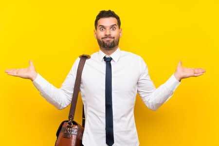 Handsome businessman over isolated yellow background having doubts with confuse face expression